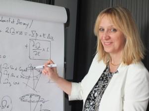 Véronique Dehant devant un tableau rempli d'équations de la rotation de la Terre.